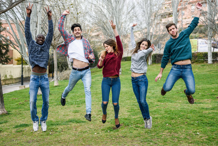 Group of young people jumping together outdoors