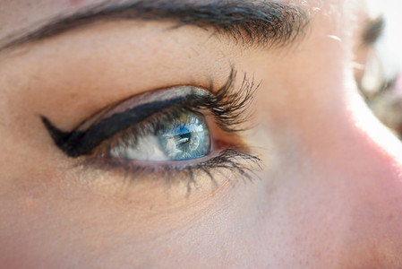 Close up of young womans blue eyes with long eyelashes