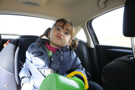Little girl traveling by car sitting in her safety seat