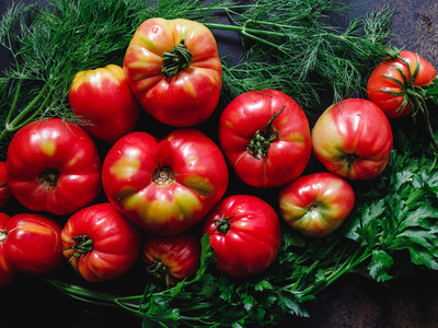 Top view of brandywine sort tomatoes with greens for seasonal salad on a table