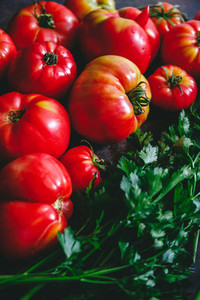 Brandywine sort tomatoes with greens for seasonal salad on a table