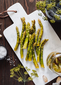 Pickled asparagus on a white marble tray Seasonal canning vegetable recipe