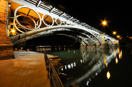 Triana Bridge over Guadalquivir river at sunset with river refle