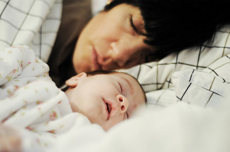 Mother and cute little baby sleeping together on bed