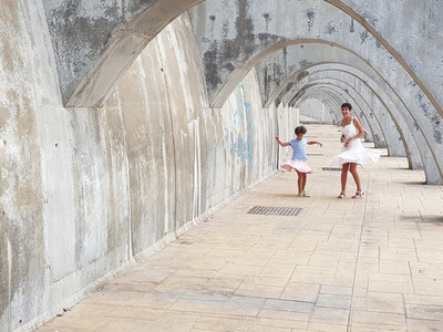Mother and daughter dancing under the arches of the Port of Mala
