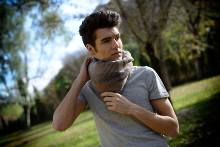 Attractive young handsome man  model of fashion in the park