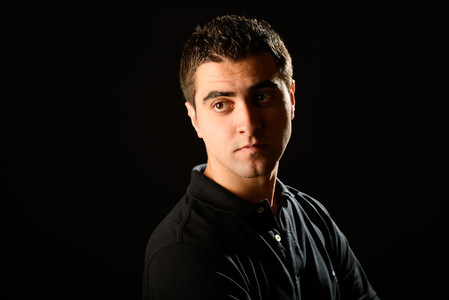 Young casual man on black background