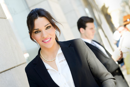 Attractive businesswoman standing outside of company building  C