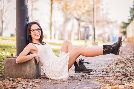 Happy girl model of fashion with high heels sitting on the floor