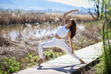 Young beautiful woman doing yoga in nature