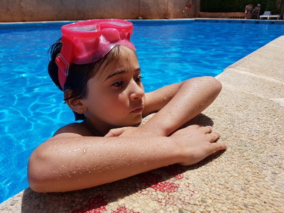 little girl bathing in a pool with diving goggles
