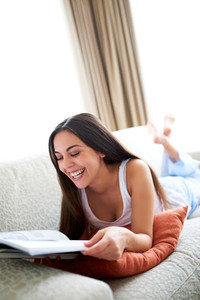 Woman lying on couch reading and laughing