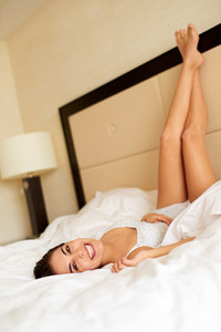 Woman lying upside down on bed smiling