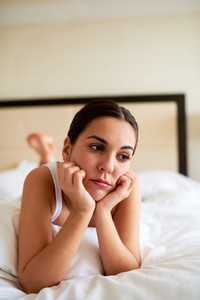 Woman lying in bed looking downcast