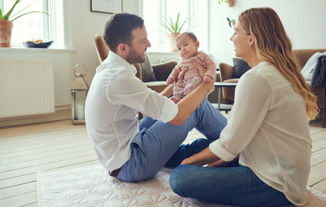 Smiling young parents sitting with their baby girl at home