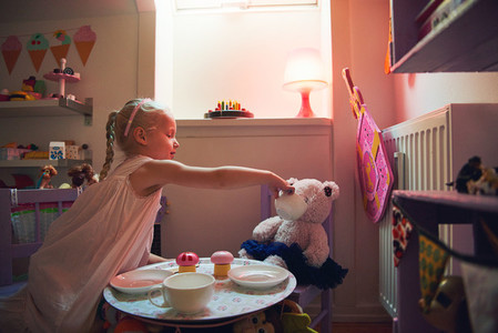 Girl playing tea party with her toy bear