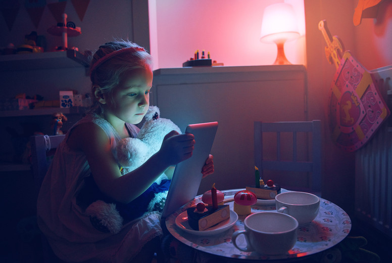 Small girl with tablet holding toy bear