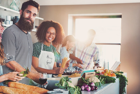 Smiling people looking at camera while cooking