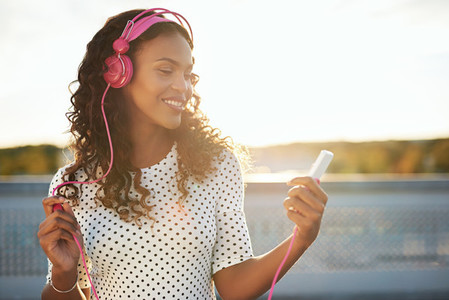 Lady listening to music in pink headphones