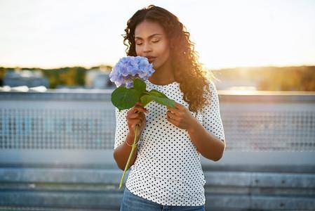 Black woman smelling a pretty flower