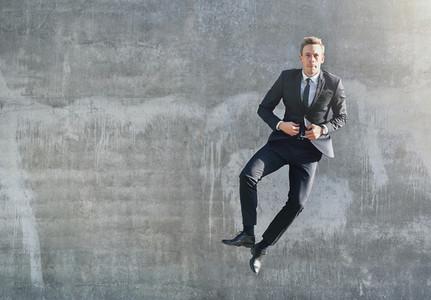A jumping happy businessman looking at camera