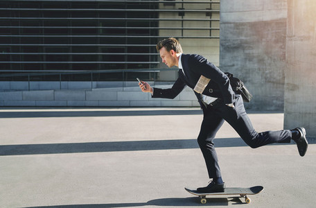 Businessman on a skateboard rushing to meeting