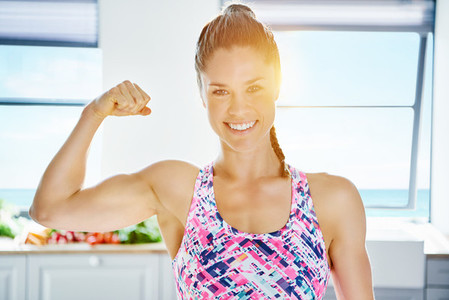 Healthy sporty woman at kitchen showing bicep