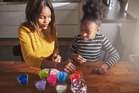 Adult female choosing beads with child at table
