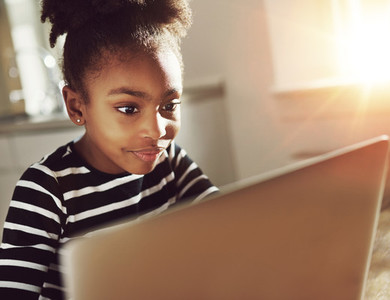 Trendy little girl using a laptop at home