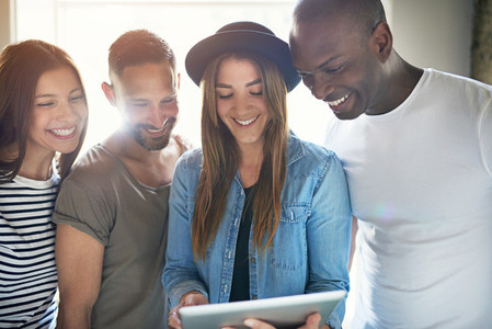 Laughing group of four adults looking at laptop