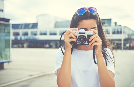 Young woman photographing the camera