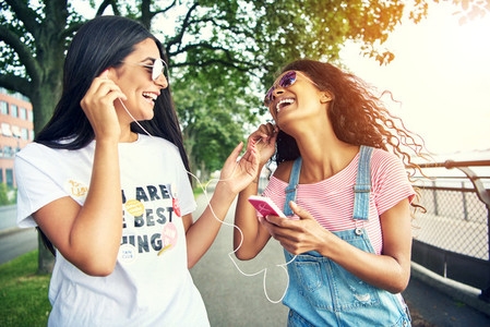 Laughing female friends listen to music