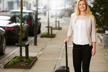 Professional white woman posing with suitcase