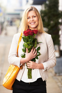 Professional woman posing with red roses