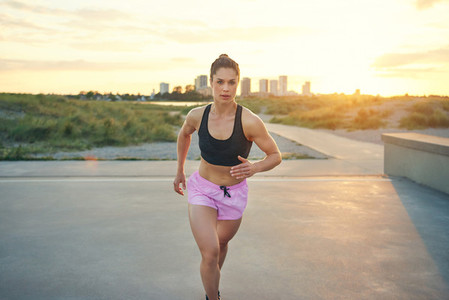Serious female jogger with pink shorts running
