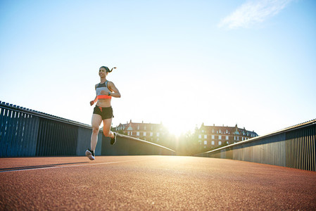 Low angle of woman running down bridge with sun