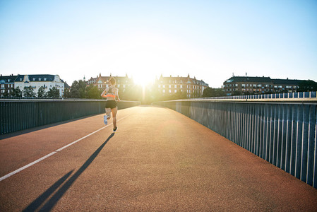 Woman running down bridge with long shadow in back