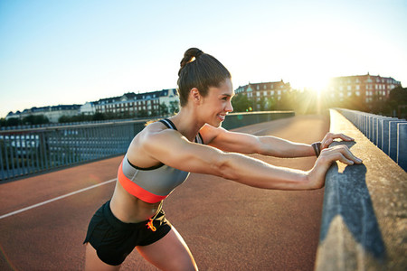 Smiling muscular jogger presses against railing