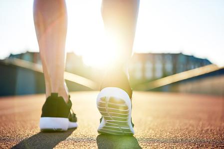Athlete preparing to run down empty road