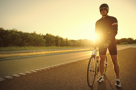 An athlete with bicycle on empty road