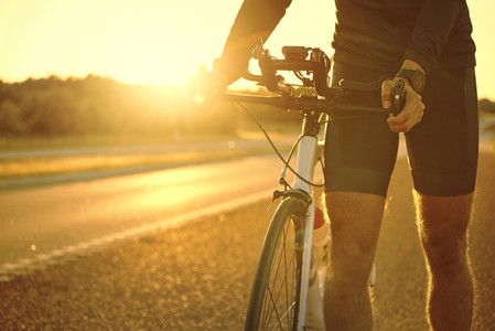Man holding bicycle on empty sunset road