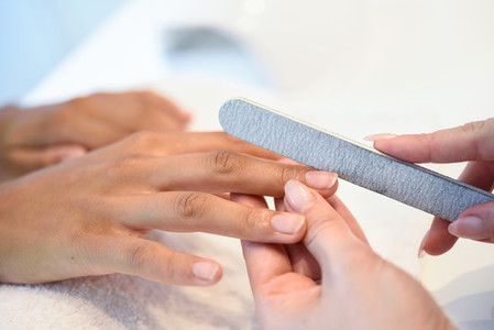 Woman in a nails salon receiving a manicure with nail file