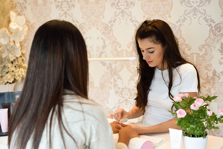 Manicure nail care for the client sitting at a table in the office