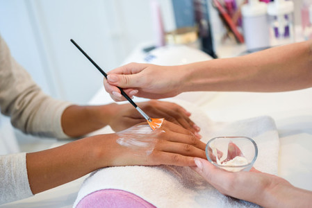 Close up of beautician applying cream on womans hand using brus