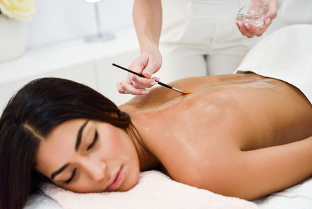 Woman receiving back massage treatment with oil brush in spa wel