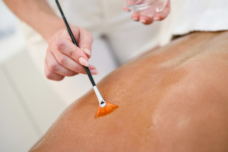 Woman receiving back massage treatment with oil brush