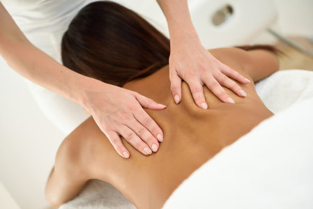 Arab woman receiving back massage in spa wellness center