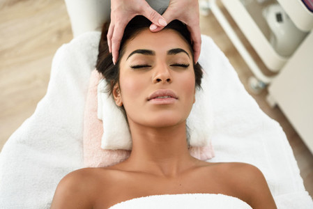 Woman receiving head massage in spa wellness center