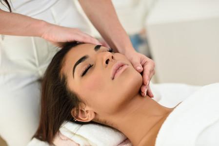 Woman receiving head massage in spa wellness center