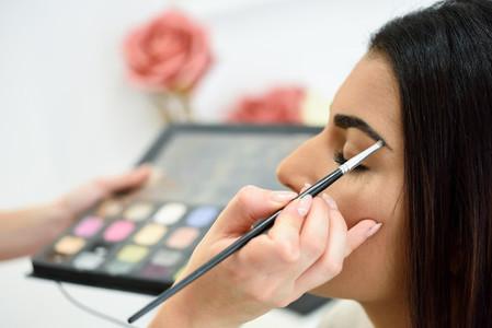 Makeup artist putting make up on an womans eyebrows